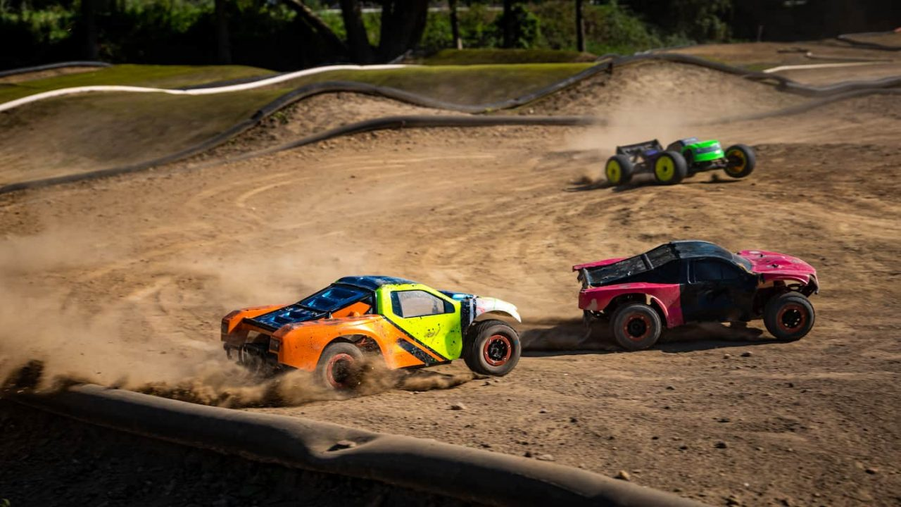 Three offroad RC cars turning into a sharp turn